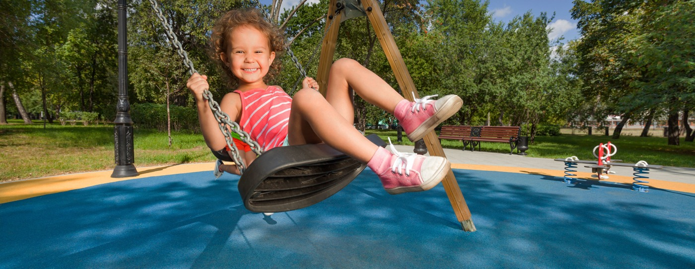 Young girl swings on commercial playground swing with a happy smile.