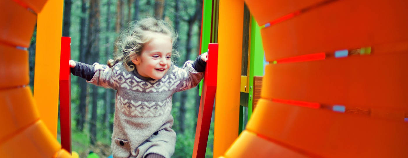 Young girl playing on a bright colored playground.