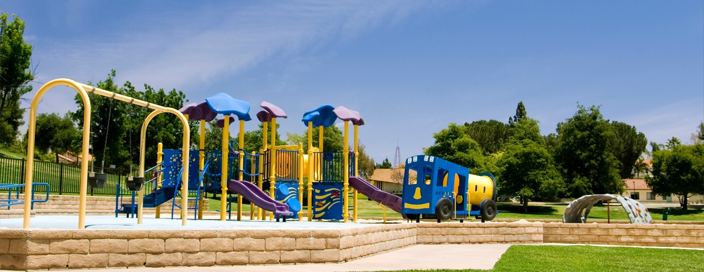 Large commercial playground with a variety of climbers, slides and panels.