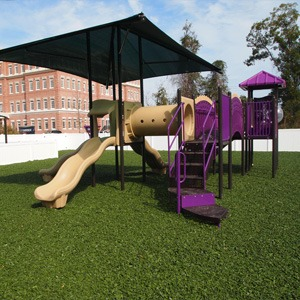Commercial playground unit with integrated shade structure and rubber playground mulch.