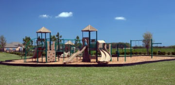 Colorful commercial playground with swings, climbing equipment and slides.