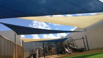 Rooftop playground, poured in place, turf and sail shades.